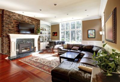 Luxury living room with stobe fireplace and leather sofas, cherry hardwood and nice rug.